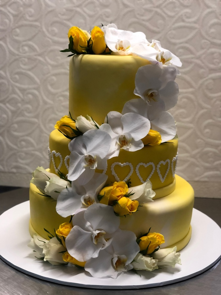 Fresh white orchids and yellow roses on a multi tier cake