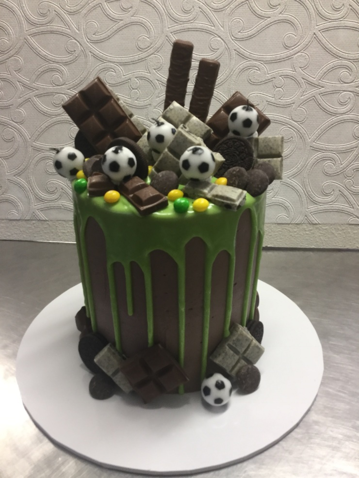 Soccer themed cake with green drip chocolate icing